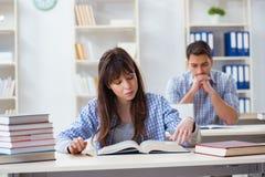 Los estudiantes que se sientan y que estudian en universidad de la sala de clase Imagenes de archivo