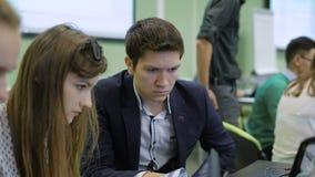 Los estudiantes se centran en solucionar el problema en la lección para los financieros futuros El hombre joven perdió en pensami metrajes