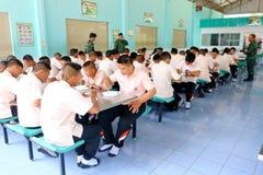 Los estudiantes tailandeses en uniforme están comiendo el almuerzo junto en el cantee imagen de archivo libre de regalías