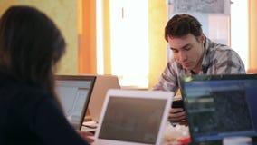 Los estudiantes trabajan en sala de clase en los ordenadores portátiles para hacer el proyecto para la lección almacen de metraje de vídeo