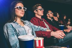 Los estudiantes tranquilos y relajados están mirando película Se están sentando juntos en una fila La gente es muy feliz Imagen de archivo