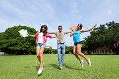 Los estudiantes universitarios felices saltan Fotos de archivo libres de regalías