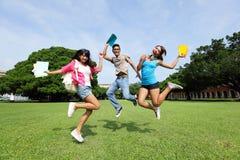Los estudiantes universitarios felices saltan Foto de archivo libre de regalías