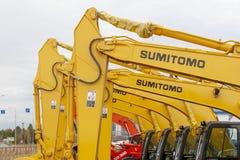 Los excavadores de Sumitomo del amarillo se alinean en una sola línea imagen de archivo libre de regalías