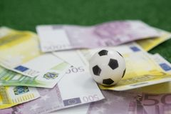 Los fútboles y las notas de la moneda arreglaron en hierba artificial Imagenes de archivo