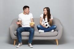 Los fanáticos del fútbol del hombre de la mujer de los pares animan para arriba el equipo preferido de la ayuda con el balón de f imagenes de archivo