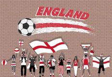Los fanáticos del fútbol ingleses que animan con Inglaterra señalan colores por medio de una bandera en frente Imágenes de archivo libres de regalías