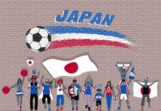 Los fanáticos del fútbol japoneses que animan con Japón señalan colores por medio de una bandera en frente Imagenes de archivo