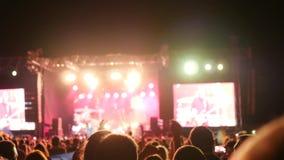 Los fans aplauden de banda de rock en luces colorantes en el concierto, palmada de la muchedumbre de manos aumentadas por encima  metrajes