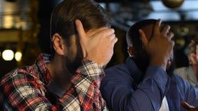 Los fans masculinos en el pub decepcionado sobre deportes preferidos combinan el juego perdidoso, facepalm metrajes