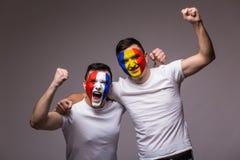 Los fanáticos del fútbol de los equipos nacionales de Rumania y de Francia celebran, bailan y gritan Imagen de archivo libre de regalías