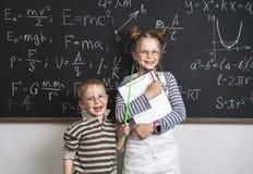Los felices alumnos del muchacho y de la muchacha se están colocando en la pizarra y los stetrads Muchas fórmulas se escriben en  fotos de archivo libres de regalías