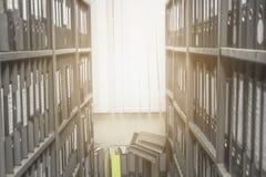 Los ficheros de documento de los estantes de una tienda se arreglan cuidadosamente dentro de la oficina imagen de archivo libre de regalías