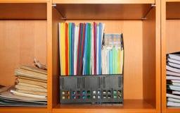 Los ficheros y las carpetas se colocan en el estante en la oficina Fotos de archivo