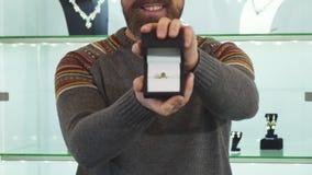 Los ficus selectivos en un anillo de compromiso en un hombre maduro de la caja se están sosteniendo