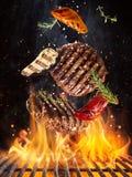 Los filetes de carne de vaca sabrosos que vuelan el arrabio antedicho rallan con las llamas del fuego fotografía de archivo