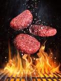 Los filetes de carne de vaca sabrosos que vuelan el arrabio antedicho rallan con las llamas del fuego fotos de archivo libres de regalías