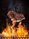 Los filetes de carne de vaca sabrosos que vuelan el arrabio antedicho rallan con las llamas del fuego fotos de archivo