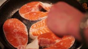 Los filetes de color salmón se fríen en una cacerola metrajes