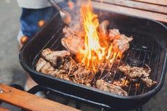 Los filetes de la parrilla en el metal rallan con la llama, barbacoa Fotografía de archivo