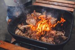 Los filetes de la parrilla en el metal rallan con la llama, barbacoa Foto de archivo