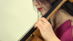 Los fingeres de la muchacha afianzan las secuencias con abrazadera en el violoncelo Vista lateral Fondo blanco almacen de video
