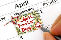 Los fingeres de la mujer con el recordatorio April Fools Day de la escritura de la pluma adentro calen Fotografía de archivo
