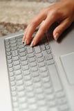 Los fingeres de la mujer en el teclado del ordenador portátil en la oficina Fotografía de archivo libre de regalías