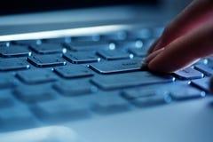 Los fingeres de la mujer en el teclado del ordenador portátil en la oficina Fotos de archivo libres de regalías