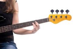Los fingeres de la mujer en la guitarra baja Fotos de archivo