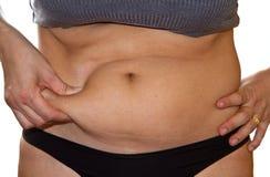 Los fingeres de la mujer que miden su grasa del vientre Fotos de archivo libres de regalías