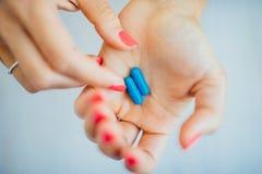Los fingeres de las mujeres con la manicura rosada que toma el azul Fotos de archivo libres de regalías