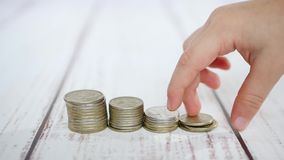 Los fingeres de un niño están tocando una pila de monedas del dinero en un fondo blanco metrajes