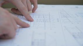 Los fingeres de un ser humano muestran el circuito en el documento impreso almacen de metraje de vídeo