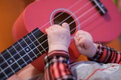 Los fingeres del bebé tocan la guitarra Secuencias y trastes del ukelele imagenes de archivo