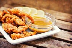 Los fingeres del pollo sirvieron con las rebanadas de la inmersión y del limón de la miel-mostaza Foto de archivo