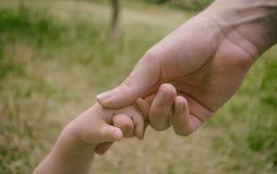 Los fingeres del ` s de los niños son sostenidos por el finger de un adulto Foto de archivo
