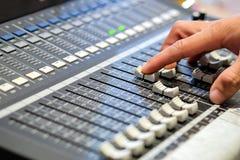 Los fingeres del ` s del ingeniero de sonido están presionando el regulador del audio del botón Fotos de archivo