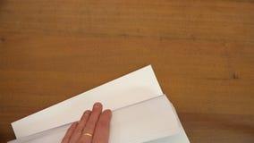 Los fingeres enrollan a través de las hojas de papel metrajes