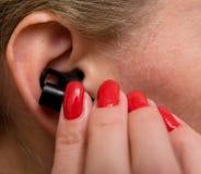Los fingeres femeninos bien arreglados hermosos insertan auriculares en su oído fotografía de archivo