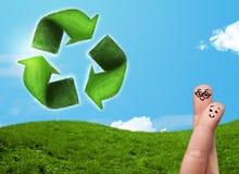 Los fingeres sonrientes felices que miran la hoja verde reciclan la muestra Fotografía de archivo libre de regalías