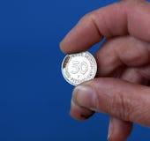 los fingeres sostienen la moneda vieja de Alemania Imagen de archivo libre de regalías