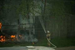 Los firemans son extinguen un coche ardiente estallado imagenes de archivo