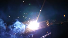 Los flashes y la porción de chispas de la soldadura trabajan en el emplazamiento de la obra en oscuridad almacen de metraje de vídeo