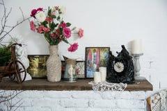 Los floreros del diseño interior con las flores y las velas registran el firep del ladrillo Imagenes de archivo