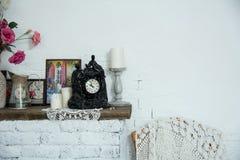 Los floreros del diseño interior con las flores y las velas registran el firep del ladrillo Fotos de archivo