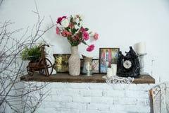Los floreros del diseño interior con las flores y las velas registran el firep del ladrillo Fotos de archivo libres de regalías