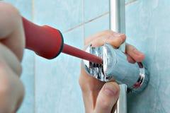 Los fontaneros dan aprietan el tornillo usi ajustable del soporte de la manija de la ducha fotos de archivo libres de regalías