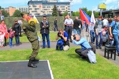 Los fotógrafos fotografían mientras que el empleado del soldado-contrato realiza ejercicios con los pesos Fotos de archivo