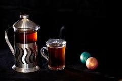 Los franceses presionan con té y una taza del té, huevos de Pascua en fondo negro Fotografía de archivo